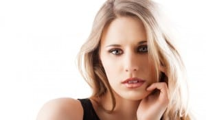 beauty portrait of a young and beautiful blond girl with long hair and natural make up posing over white, she looks in to the lens and her left hand is near the face