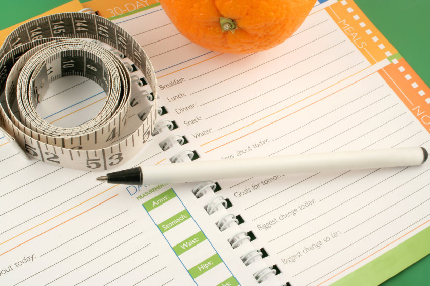 writing in a diet and nutrition journal with orange to the side