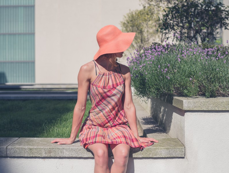 A young woman wearing a dress and a hat is relaxing outside an apartment building on the lawn by some lavender