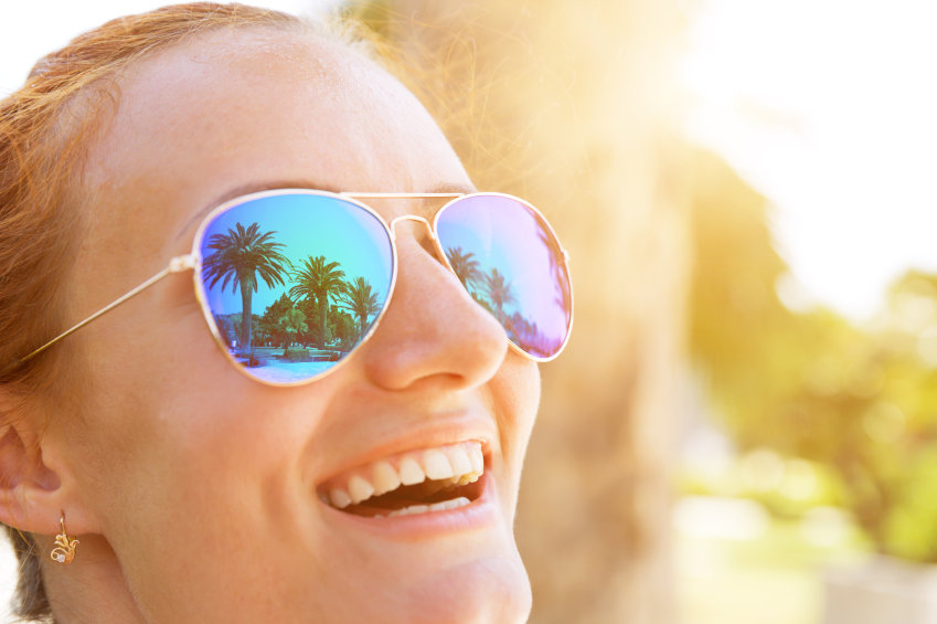 Palm trees reflect in the happy girl sunglasses
