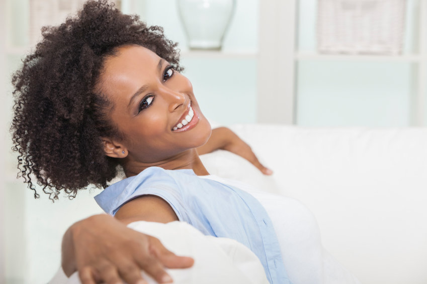 A beautiful mixed race African American girl or young woman sitting on sofa at home looking happy and relaxed