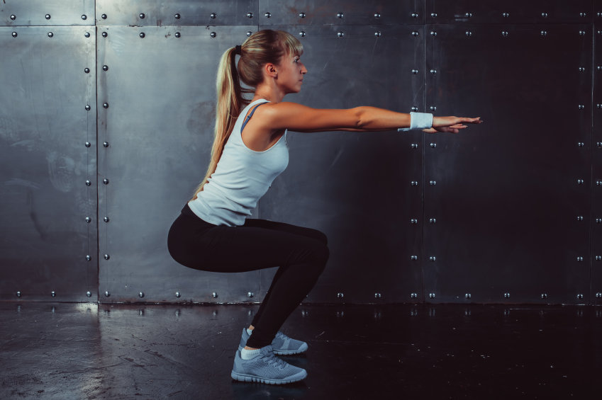 Athletic young woman fitness model warming up doing squats exercise for the buttocks concept sport slimming healthy lifestyle.