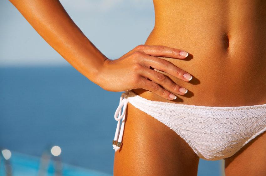 Beautiful young Sexy woman body in bikini during sunbath next to swimming pool